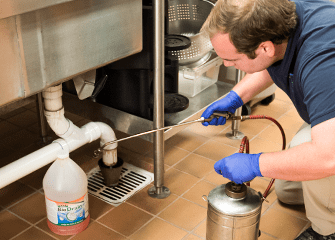 commercial pest control tech getting rid of pests in local business
